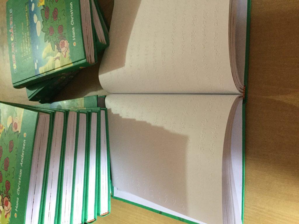 Foto en el que se ve una Pila de libros Braille junto a un libro abierto